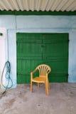 在一个绿色门前面的黄色椅子 库存照片