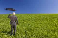 在一个绿色领域的商人与伞 免版税库存照片