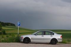 在一个绿色领域的银色汽车停车处 免版税库存照片