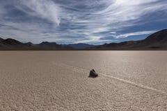 在一个破裂的干盐湖地板上的航行石头 库存图片