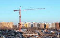 在一个建造场所的红色和白色大厦塔吊反对现代大厦背景  在起重机的焦点 免版税库存照片