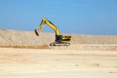 在一个建造场所的黄色挖掘机反对蓝天 免版税库存照片