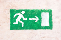 在一个黑门道入口上的紧急出口标志 免版税库存图片