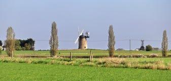 在一个n英国农村风景的风车与庄稼的领域 免版税图库摄影