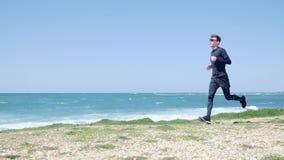 在一串足迹的幼小强的赛跑者沿穿黑体育服装的海滩 t 股票录像