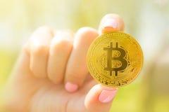 在一代阿尔法的金黄bitcoin在手中哄骗手,与bitcoin的不确定性未来的生活 免版税库存图片
