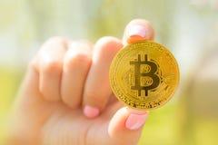 在一代阿尔法的金黄bitcoin在手中哄骗手,与bitcoin的不确定性未来的生活 图库摄影
