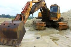 在一件含沙猎物的黄色强有力的挖掘机 库存照片