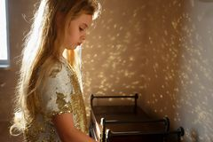 在一件巧妙的礼服打扮的一个七岁的女孩装饰用金闪闪发光在屋子,阳光里站立 免版税库存图片