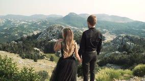 在一件巧妙的长的礼服和一个人的美好的爱恋的夫妇少妇模型摆在照相机的一套黑衣服的反对a 股票视频