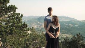 在一件巧妙的长的礼服和一个人的美好的爱恋的夫妇少妇模型摆在照相机的一套黑衣服的反对a 影视素材