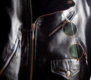 在一件散布的夹克的一个口袋的时髦葡萄酒圈子太阳镜 库存图片