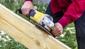在一件深红衬衣的男性手拿着一台黄色研磨机并且处理一个木板 免版税库存图片