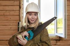 在一件白色盔甲的年轻淘气白肤金发的女孩建造者与一把锯、一个水平和一个手机在房子的建造场所在 免版税库存图片