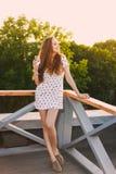 在一件白色短的夏天礼服的美丽的年轻性感女孩微笑牙的画象在橙色日落a  免版税图库摄影