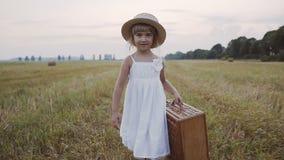 在一件白色礼服穿戴的草帽的美丽的小女孩在领域在她的手上走并且拿着秸杆篮子 影视素材