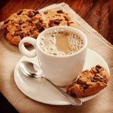 在一件白色衬衣和饼干的芬芳咖啡在桌上 免版税库存图片