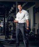 在一件白色衬衣的时髦,典雅的男性举行在健身房的哑铃 库存图片