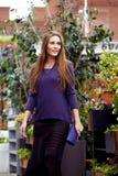 在一件紫色毛线衣和一条时髦的黑暗的长的裙子打扮的时兴的女孩在公园走 库存照片