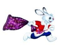 在一件红色外套的白色蓬松兔子迅速跑在右边,拿着与礼物的一个紫色袋子圣诞节的 隔绝,手拉 库存图片