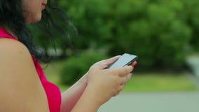 在一件红色礼服的女性手键入在他们的电话的SMS 特写镜头 影视素材