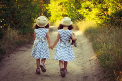 在一件美丽的礼服和秸杆夏天帽子的两个逗人喜爱的curlz孩子走开在森林或公园路的 拿着孪生的现有量 小孩f 免版税库存照片