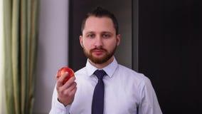 在一件衬衣的有领带的吃苹果的一个成功的有胡子的商人的画象 一种健康生活方式的概念 股票录像