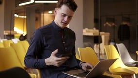 在一件逗人喜爱的衬衣的年轻可爱的男性微笑,当拿着智能手机和键入某事在他的膝上型计算机对同样时的 影视素材