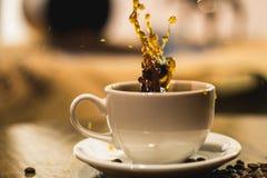 在一份咖啡的飞溅在一个白色杯子 图库摄影