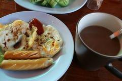 在一份蓝色板材和热的咖啡和荷包蛋投入的香肠 免版税库存照片