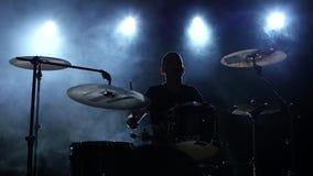 在一位专业鼓手的表现的精力充沛的音乐 黑发烟性背景 剪影 慢的行动 股票视频