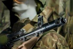 在一位战士的制服的时装模特有枪的 免版税库存图片