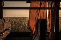 在一位老葡萄酒教练赢得的空的公共汽车席位在日落期间,领域在背景中能看 免版税库存图片
