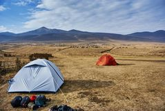 在一使荒凉的moutain风景ar的白色和红色橙色生动的帐篷 库存图片