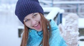 在一冷的冬天雪watercoast温暖地穿衣的被编织的帽子的愉快的女孩显示舌头在照相机并且摇她的手 图库摄影