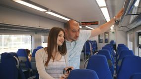 在一列市郊火车的年轻夫妇骑马 股票录像