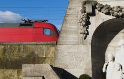 在一列现代火车前面的历史的墓地墙壁 免版税库存照片
