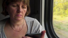 在一列移动的火车的窗口的附近年轻女人由电话沟通 影视素材