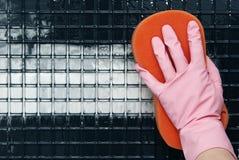 在一副桃红色手套的一只手 免版税库存图片