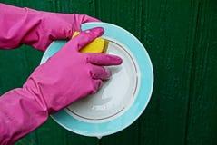 在一副红色手套的手洗涤与盘的洗碗布 库存照片