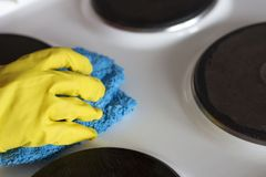 在一副黄色手套的一只女性手洗涤与旧布的电火炉 免版税库存照片