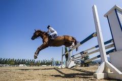 在一匹马的未知的车手在竞争时匹配乘坐在周围 免版税库存图片