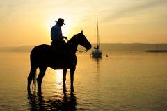 在一匹马的车手在日出 库存图片
