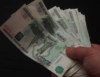 在一千卢布的衡量单位的钞票在person& x27的; s 库存照片