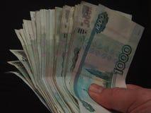 在一千卢布的衡量单位的钞票在person& x27的; s 免版税库存图片