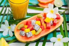 在一半的热带水果沙拉番木瓜用芒果汁,在五颜六色的木背景的圆滑的人 顶视图 库存图片
