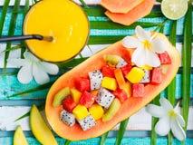 在一半的热带水果沙拉番木瓜芒果汁 免版税图库摄影