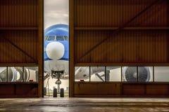 在一半被打开的门前面的飞机对飞机棚 免版税库存图片