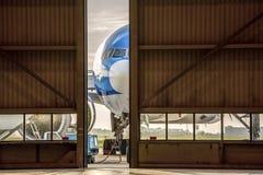 在一半被打开的门前面的飞机对飞机棚 库存照片