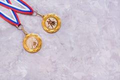 在一卷磁带上的两枚奖牌在灰色背景 库存图片
